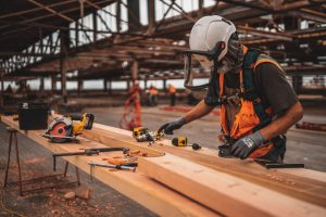 man in orange and black vest wearing white helmet holding yellow and black power tool